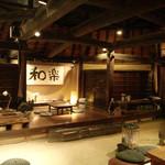 23037085 - 古材の梁と土間の広々店内。和楽の舞台にも席が