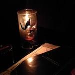 ヴァンパイア カフェ - 照明用にテーブルに置かれたアルコールランプと、ドリンクのメニューが載った棺の冊子。
