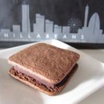 バニラビーンズ - ショーコラ(通常価格368円)クッキー生地でチョコを挟んでいます。チョコというより、焼き菓子のような印象。お店の一番人気商品のようです。   黒い紙袋も素敵♪みなとみらいのイラストが描かれています。