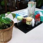 飯田食堂 - @卓上セット内容写真 ・植物 ・ティッシュ ・醤油 ・爪楊枝 ・割り箸 ・ソース ・胡麻塩 ・七味 ・胡椒 ・湯呑茶碗 ・お茶入りポット