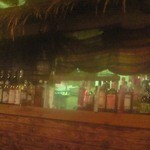 南風荘 - カウンターはわらぶき屋根をイメージした東南アジア風で、酒瓶が並べられています