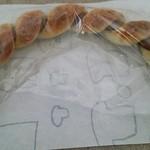 24404686 - スパイシーロングソーセージ。優に30㎝はあるピリ辛ソーセージに、もっちりとしたパンが巻き付いている。