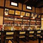 にきたつ庵 - カウンター席は喫煙可。日本酒がずらりと並ぶ様は圧巻