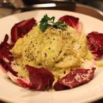 プッチー - ピスタチオのカルボナーラ (黒トリュフの香りとハーブ野菜の苦みを合わせました)