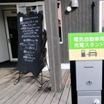 タパ - 電気自動車用充電スタンドの隣が入り口