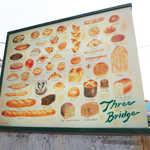 スリーブリッヂ - 看板には、各種パンのイラスト。ひとつだけ、パンじゃないものも(^-^)