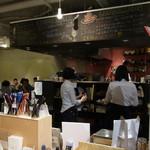 文房具カフェ - オープンキッチンの周りにはテーブルのほか文房具を並べた棚が並んでいます