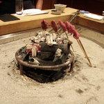 柳家 - こうやって囲炉裏の炭火で焼かれていきます