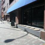 ザ シティ ベーカリー - 朝陽に照らされる店先。店先にはベンチが。