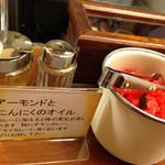 辛激屋 - 卓上には、福神漬け・アーモンドとニンニクの粒々入りオイル・ココイチのとび辛スパイス的パウダー。 アーモンドとニンニクの粒々入りオイルを入れると、香ばしくて美味しかったです。