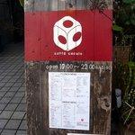 カフェ・ココロ - 店前の看板です。木の板の上に赤と白でペインティングしてロゴが描かれています。このロゴがいい感じなんですよね。好きなデザインです。