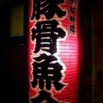 麺や高倉二条 - 店前にあった提灯です。この大きな提灯が目立っているんですよね。遠くからも良く見えてました。真っ赤な提灯に大きく 豚骨魚介 って書いてますね。右横には全粒粉麺って書いてます。