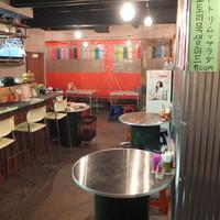 トモネポチャ - 店内は韓国の屋台をイメージしたオレンジ色のテントとドラム缶テーブル