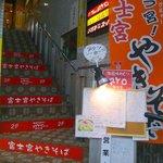 諸国味めぐり RYO - お店はビルの2階にあります。この階段をテクテクと登っていく訳です。階段の所にもオレンジで広告が入っていますね。右手には「う宮(ウミャー)」のノボリがありますよ。このノボリは富士宮の現地でも至る所でみま