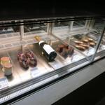 つもん - 焼き菓子、タルト、ケーキとワインが並ぶショーケース。