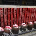 聚中縁餃子 - お店の横に並ぶ赤いメニューと壺