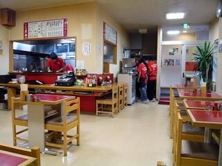 らーめんや天金 四条店 - 一番奥から入口方面を撮っています。店内は赤いテーブル席なんですね店員さんのTシャツも真っ赤ですし、暖簾も真っ赤でしたね。