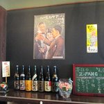 たこ焼き ジパング - 焼酎と日本酒の一升瓶が並ぶ棚、日ごとに増えてきている