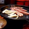 オンマ家 - 料理写真:サムギョプサル(980円)。2人前からオーダー可。エリンギや玉ねぎと一緒におやじさんがつきっきりで焼いてくれます。写真のお肉でちょうど1人前分くらいかな。