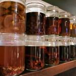 韓国旬菜ハル - カウンターの前には薬用酒・果実酒が並ぶ。