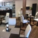 金の百合亭 - しっくい壁の白と天然木の茶を基調にした、落ち着いた雰囲気の店内。