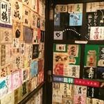 酒縁川島 - 日本酒のラベルが貼られた玄関の引き戸と内壁