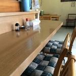 二代目おかだラーメン - L字形カウンターとテーブル席のある店内
