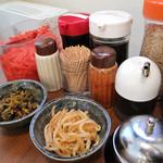 いせちゃん - 卓上。ピリ辛モヤシと辛子高菜はセルフコーナーで小皿に取り放題。