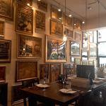 トラットリアチッチョ - 絵画が壁一面に飾ってあります。