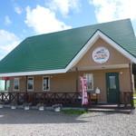 べこちちファクトリー - 広い砂利敷きの場所に、緑の屋根のログハウス