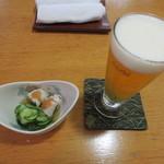 31587504 - 生ビール(500円+税)にお通しは鱧の梅肉あえ。