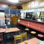 九州ラーメン 日吉 - 合板の壁とデコラのテーブルのレトロな店内。