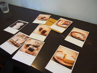 エランズカフェ - メニューがポストカード風。裏面に商品説明があります。