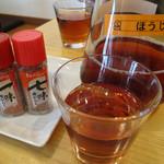 かんた - 卓上にはワサビではなく一味と七味。 そして、お冷代わりの冷たいほうじ茶。 とてもマイルドで美味しいです。