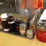 はかたや - 卓上。 辛子高菜は有料サービスになってます。 辛子高菜ラーメンは基本に100円アップの390円。