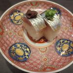 33230449 - サンマの押し寿司。上に茶色のサンマのわたの塩辛、緑色の葱と生姜を刻んで和えたものが。