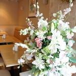 34053797 - 窓の際の席と、奥の席を仕切る生け花