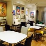 ワサビカフェ - アニメーションの背景画やセル画が飾られた店内