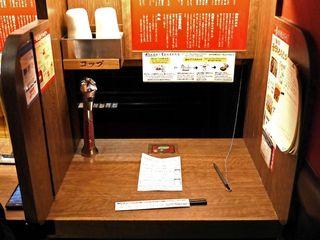 一蘭 アトレ上野山下口店 - 特許取得済みの一蘭名物『味集中カウンター』と、 テーブルの上には『オーダーシート』。