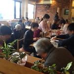 34467946 - 店内テーブル席。お客さんで賑わっています。