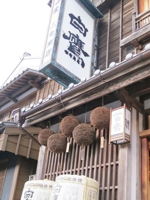 白鷹三宅商店 - 年期の入った看板に杉玉が吊るしてあります