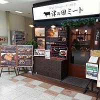津の田ミート - シックな木目とレンガ調のデザインの外観です。店頭の黒板や額でこだわりやメニューを告知しています。