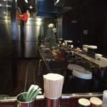 あかばね濱家 - カウンター席より望む厨房。冷蔵庫手前上に謎のカーブミラーが(笑)