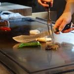 36462834 - 鉄板の上で肉を焼く前に野菜をカット