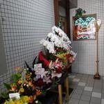 ちぃりんご - 入口には祝花が