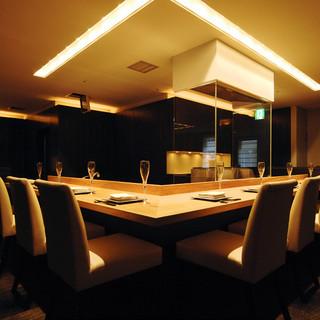 白木のダブルカウンター、落ち着いた間接照明、高級感溢れる個室