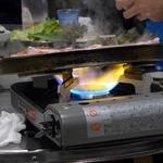 新宿ポジャンマチャ - 鉄板を斜めにして脂を流しながら焼いている