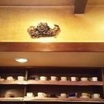 くらもち珈琲 - 壁のカップ棚の上のモニュメント