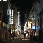 笑座こんぱる - コンパル通り沿い、右の青い照明が金春湯、先の赤い看板が笑座こんぱる