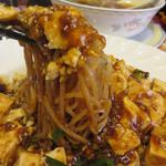 37795424 - 炒めて焼き付けた麺にたっぷりの麻婆豆腐をかけたものです。                       コクがあってピリ辛の麻婆豆腐。                       粘度はポッテポテです。